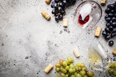 Red and white wine. With glass, bottle and grapes over gray stone background, copy space , top view stock photos