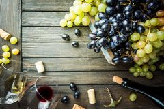 Red and white wine. With glass, bottle and grapes over wooden background, copy space , top view stock photos