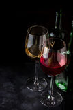 Red and white wine in glasses and bottles on dark background. Royalty Free Stock Images
