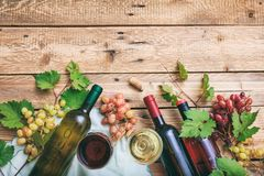 Red and white wine glasses and bottles on wooden background, copy space. Fresh grapes and grape leaves as decoration Stock Photography