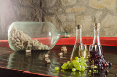 Red and white wine with glasses and bunches of grapes. A shot of red and white wine with glasses, bunch of grapes, big bottle full of corks and stone wall in the Royalty Free Stock Photo