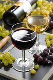 Red and white wine in glasses, fresh grapes in the background Stock Photo