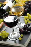 Red and white wine in glasses, fresh grapes in the background Stock Photography