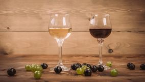 Red and white wine glasses and grape on wooden table stock photos