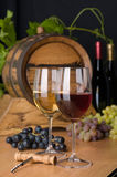 Red and white wine with grapes. And a wine barrel royalty free stock image