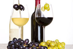 Red and white wine with grapes. In the foreground Royalty Free Stock Photos