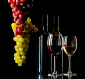 Red and white wine with grapes. Red and white wine in bottles and wineglasses and bunches of grapes on black background Royalty Free Stock Photo
