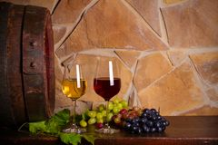 Red and white wine with grapes beside old cask in wine cellar. Glasses and bottles of wine on wooden table. Horizontal royalty free stock images