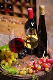 Red and white wine with grapes on old cask in wine cellar. Vertical stock image