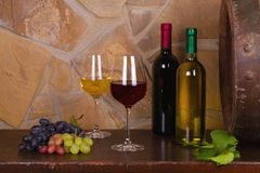 Red and white wine beside old cask in wine cellar. Red and white wine beside old cask in wine cellar stock photos