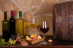 Red and white wine beside old cask in wine cellar. Red and white wine bee old cask in wine cellar stock photo