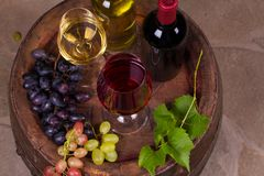 Red and white wine on old cask in wine cellar. Wine and food concept. Red and white wine on old cask in wine cellar. Wine and food concept, overhead Stock Photos