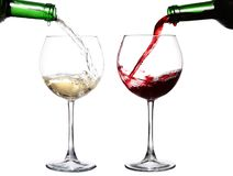 Red and white wine poring in two glasses royalty free stock image