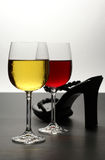 Red and white wine with shoe. Red and white wine with a sexy female shoe on bi-colored background Stock Images