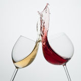 Red and white wine splash. Toasting gesture red and white wine with big splash big splash Stock Photos
