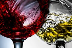 Red and white wine splash in wineglasses close-up macro.  royalty free stock photography