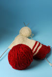 Red and white yarn balls with knitting needles. On a blue background Royalty Free Stock Images