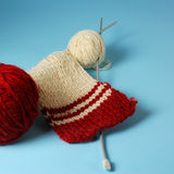 Red and white yarn balls with knitting needles. Over blue background Stock Photos