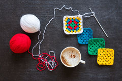 Red and white yarn, crocheted motives and coffee Stock Image