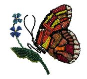 Red with white, yellow and black butterfly beads. Butterfly with red, yellow, white and black wing sitting on a flower flies beads needlework embroidery royalty free stock image