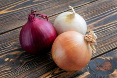 Red, white and yellow onions on wooden background royalty free stock photo
