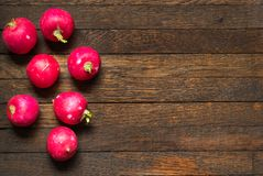 Red whole radishes on wooden table with copy space. Red, raw, whole radishes on dark brown wooden table. Copy space. Objects in left position. Close up stock photo
