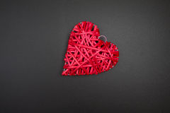Red wicker heart on blackboard. Postcard to Valentines Day. Stock Photos