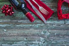 Valentine`s day concept. Red wicker heart,bottle of red wine,red napkin and cutlery on old paint wooden background with copy space Stock Images