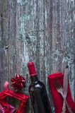 Romantic dinner concept. Red wicker heart,bottle of red wine,red napkin and cutlery on old wooden background with copy space, vertical picture Royalty Free Stock Photography