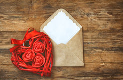 Red wicker heart with roses, envelope with blank note Royalty Free Stock Image