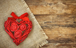 Red wicker heart with roses and ribbon, canvas napkin Royalty Free Stock Photos