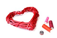 Red wicker heart and spools of thread. stock photography