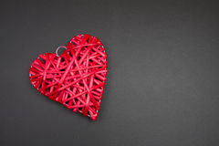 Red wicker rattan heart on black chalkboard. Valentines Day. Stock Image