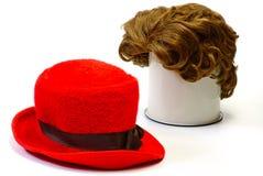 Red wig and  red bonnet. Red wig and red  bonnet on white isolated Stock Photography