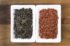 Red and wild rice in white the bowls on wooden background Stock Photos