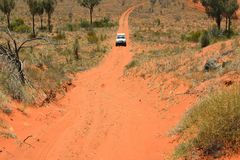 Red wild road. Red Australian wild road with approaching white off road car. Northern Territory, Australia Royalty Free Stock Photo