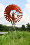 Red wind mills in grass field Stock Photo