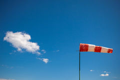 Red wind vane against a blue sky Royalty Free Stock Photo