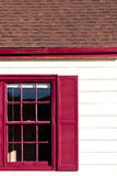 Red windon and gutters accent on the white house Royalty Free Stock Photo