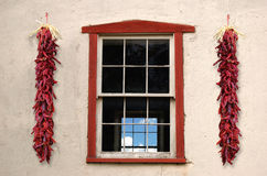 Red Window. Frame found on old adobe building with two chili ristras Stock Image