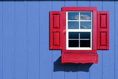 Red window. On blue wall with cloudy sky reflecting in glass royalty free stock image