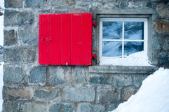 Red window. A picture of a red classic window of a mountain house in winter Stock Photo