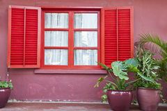 A red window. A ren window on a pink wall Royalty Free Stock Photos