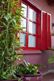 A red window. A ren window on a pink wall Royalty Free Stock Photography