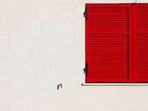 Red Window. A minimalistic picture of a red classic window on a sunny white wall Royalty Free Stock Photography
