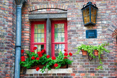 The red window. Red window frame with red geraniums in plants pots on the window ledge. An old lamp attached to the wall above and to the right of the window Royalty Free Stock Images