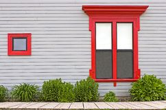 Red Window Frames. In a grey wooden building Royalty Free Stock Image