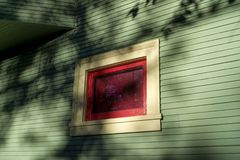 Red window on green house Stock Photo