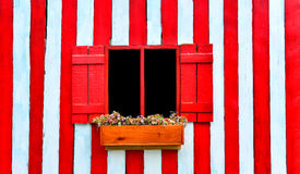 Red window on red and white wooden wall. And flower in wooden vase Stock Photo