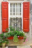 Red Window Shutters with Flower Box and Planter. Red window shutters with flower box, planter and wrought iron decoration photographed in Charleston, South Stock Photos